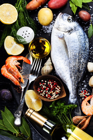 wine stocks: Delicious fresh fish and seafood on dark vintage background.