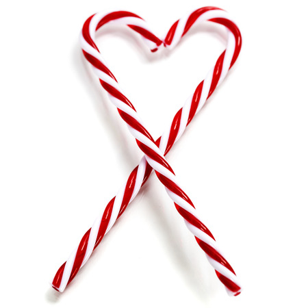 Two Candy Canes in Heart Shape over white photo