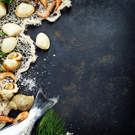 Delicioso pescado fresco y mariscos en el fondo oscuro de la vendimia. Los peces, almejas y camarones con hierbas aromáticas, especias y verduras