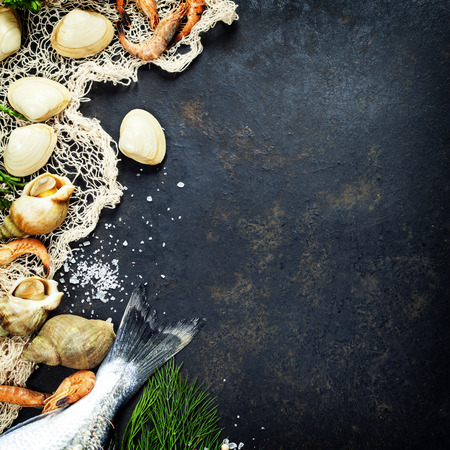 Delicious fresh fish and seafood on dark vintage background. Fish, clams and  shrimps with aromatic herbs, spices and vegetables