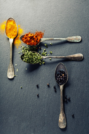 herbs: Herbs and spices selection - herbs and spices, old metal spoons and slate background Stock Photo