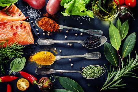 健康食品,飲食或烹調的概念 - 新鮮的鮭魚片用香草,香料和蔬菜美味的部分 版權商用圖片