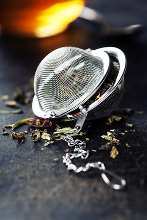 Tea composition with tea strainer on dark background photo