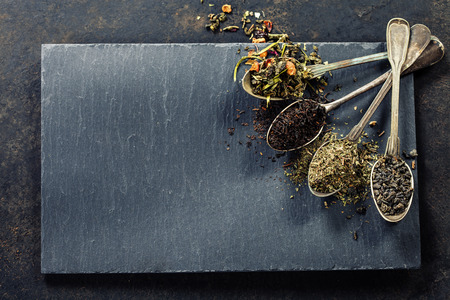 india food: Tea composition with Different kind of tea and old spoons on dark background