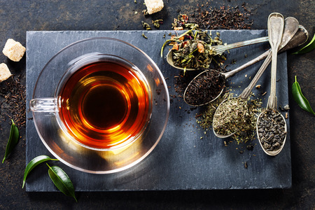 hot beverage: Tea composition with old spoon on dark background Stock Photo