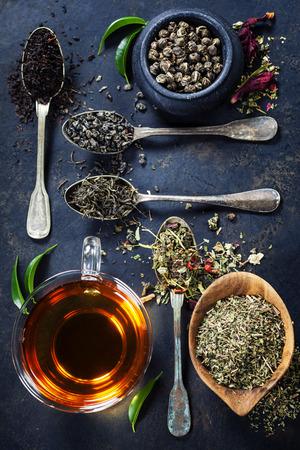Tea összetétele különböző típusú tea és a régi kanál sötét háttér