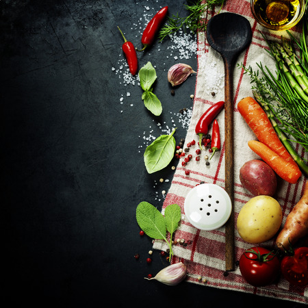 Wooden spoon and ingredients on dark background Imagens