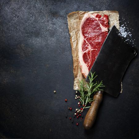 cutelo vintage e bife de carne crua no fundo escuro Imagens