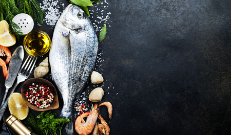 peces: Delicioso pescado fresco en el fondo oscuro de la vendimia. Pescado con hierbas arom�ticas, especias y verduras - comida sana, dieta o concepto de cocina Foto de archivo