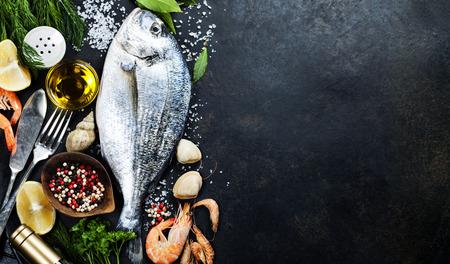 Heerlijke verse vis op een donkere vintage achtergrond. Vis met aromatische kruiden, specerijen en groenten - gezonde voeding, dieet of koken begrip Stockfoto