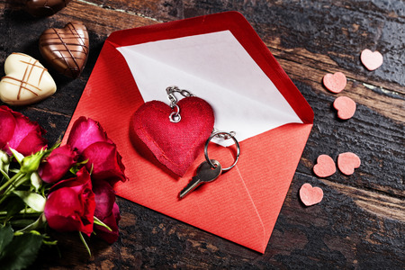 envelop: Red  envelop, roses, chocolate and key On old wood background Stock Photo