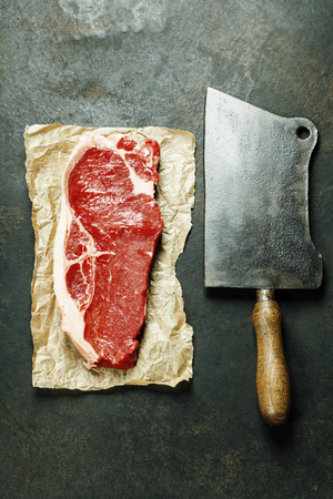 the cleaver: vintage cleaver and raw beef steak on dark background