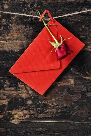 envelop: Red  envelop and rose  hanging on the clothesline. On old wood background
