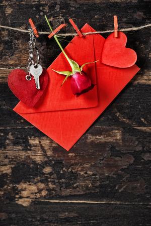 envelop: Red  envelop, key and rose  hanging on the clothesline. On old wood background