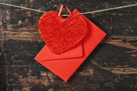envelop: Red  heart and envelop  hanging on the clothesline. On old wood background