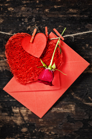 envelop: Red  hearts, rose and envelop  hanging on the clothesline. On old wood background