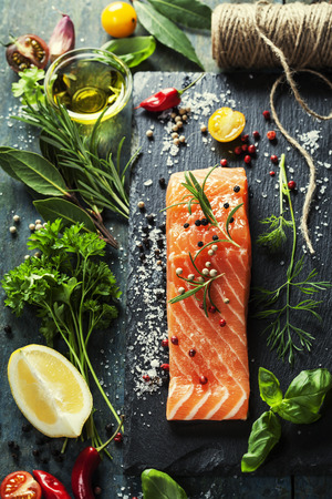 steaks: Delicious  portion of fresh salmon fillet  with aromatic herbs, spices and vegetables - healthy food, diet or cooking concept Stock Photo