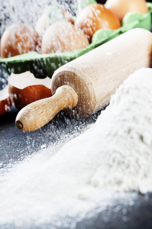 baking ingredients: baking background with raw eggs, rolling pin and flour