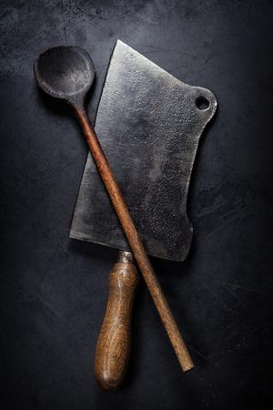 古い木のスプーンと暗い背景の上に肉包丁ナイフ