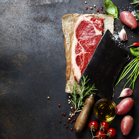 vintage cleaver and raw beef steak on dark background photo