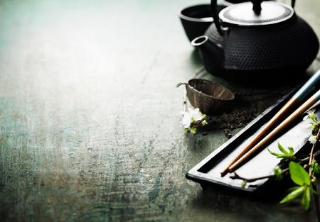mariscos: Conjunto de t� chino, palillos y la ramificaci�n de sakura en la mesa de madera r�stica