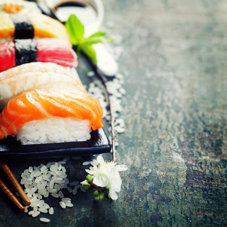 古い木製の背景に箸で寿司