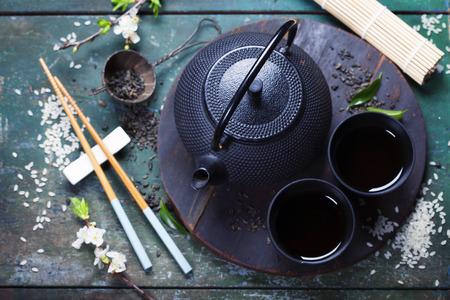 Conjunto de té chino y los palillos en la mesa de madera rústica