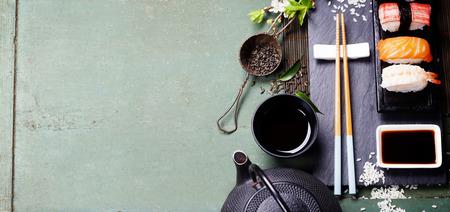 アジア食品背景 (黒鉄お茶セットと無作法なテーブルの上寿司) 写真素材