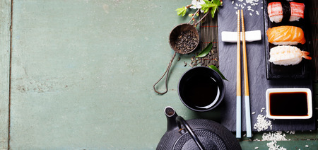 Asian food background (black iron tea set and sushi on rustic table) Stock Photo