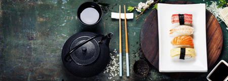 sushi menu: Asian food background (black iron tea set and sushi on rustic table) Stock Photo