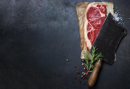 cuchilla vintage y filete de carne cruda sobre fondo oscuro