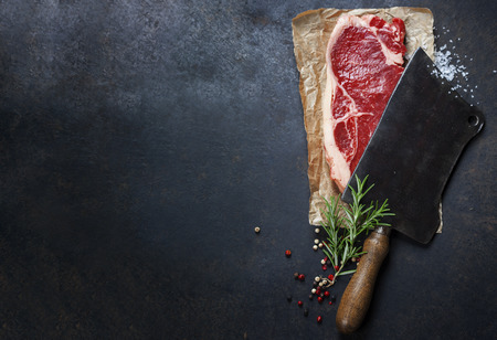 fillet: vintage cleaver and raw beef steak on dark background