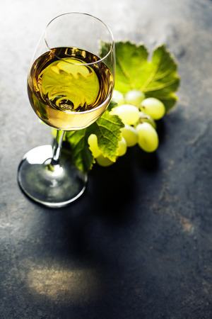 Glass of white wine on dark background Archivio Fotografico