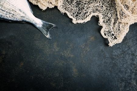 fish: Pescado con red de pesca en el fondo oscuro de la vendimia