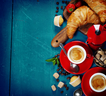 Breakfast with coffee, croissants and berries. Blue background Imagens