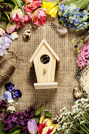 country life: Easter background with bird house, eggs, nest and flowers Stock Photo