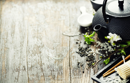 Jogo chinês Tea, pauzinhos e sakura ramo em tabela de madeira rústica