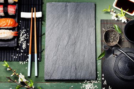 Asian food background (black iron tea set and sushi on rustic table) Stockfoto