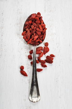 superfruit: Metal tablespoon of dried goji berries on wooden background