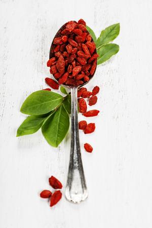 goji berry: Metal tablespoon of dried goji berries on wooden background
