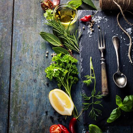 ハーブ、スパイス、オリーブ オイル、塩、レモン、野菜と食品の背景。スレートと木材の背景。