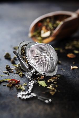 tea strainer: Tea composition with tea strainer on dark background