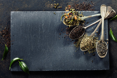 Composición del té con diferentes tipos de té y cucharas antiguas sobre fondo oscuro