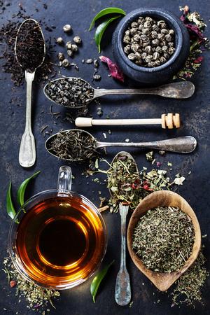 Composição do chá com Diferentes tipos de chá e colheres velhas no fundo escuro Imagens
