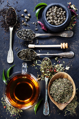 Theesamenstelling met verschillende soorten thee en oude lepels op een donkere achtergrond