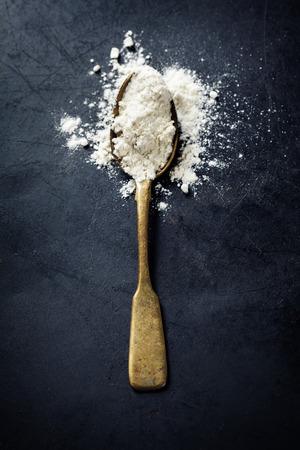 un cook: Whole flour in spoon on dark vintage background