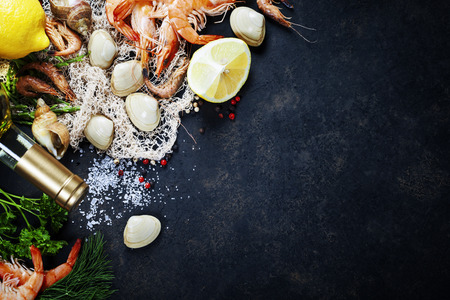 ingredient: Delicious fresh fish and seafood on dark vintage background. Fish, clams and  shrimps with aromatic herbs, spices and vegetables - healthy food, diet or cooking concept Stock Photo