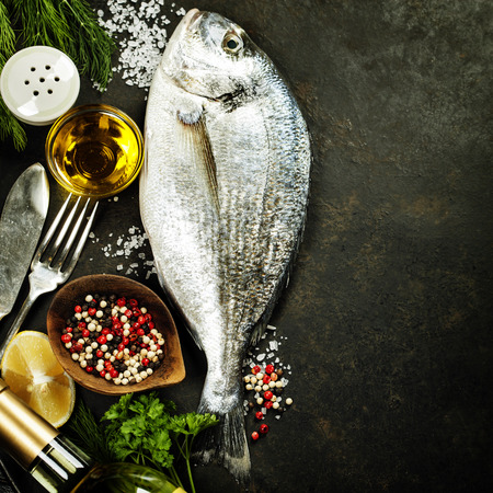 Delicious fresh fish on dark vintage background. Fish with aromatic herbs, spices and vegetables - healthy food, diet or cooking concept photo