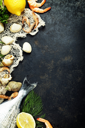 Delicious fresh fish and seafood on dark vintage background. Fish, clams and  shrimps with aromatic herbs, spices and vegetables - healthy food, diet or cooking concept Standard-Bild