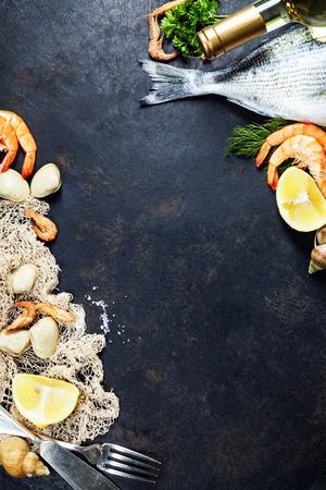 Heerlijke verse vis en zeevruchten op een donkere vintage achtergrond. Vis, mosselen en garnalen met aromatische kruiden, specerijen en groenten - gezonde voeding, dieet of koken begrip